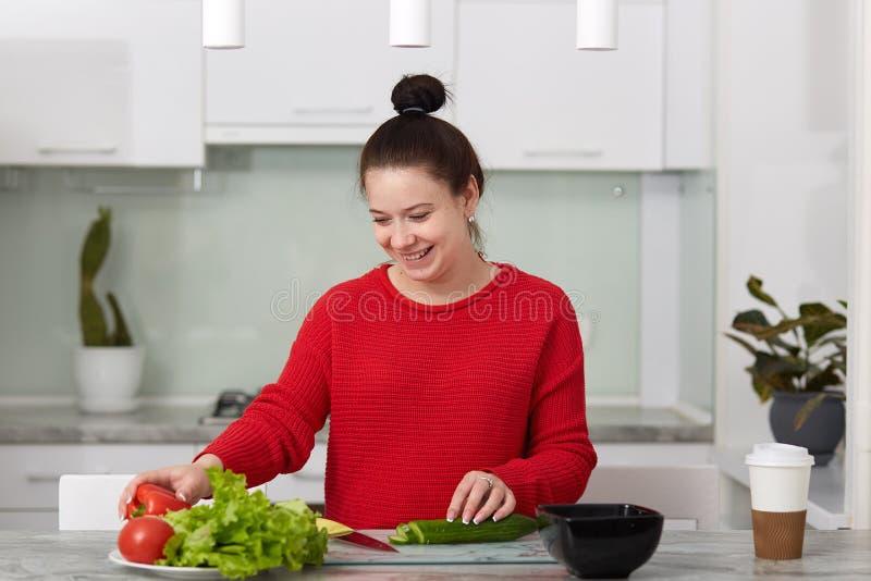 O tiro horizontal da mulher gravida de sorriso feliz corta vegetais para fazer a salada, poses contra o interior da cozinha, vest fotografia de stock
