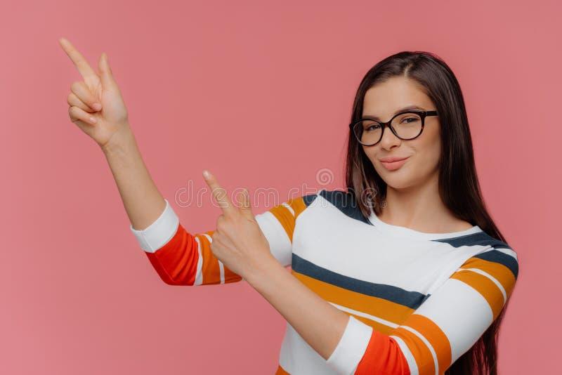 O tiro horizontal de pontos morenos bonitos da mulher para cima sobre o fundo cor-de-rosa, anuncia algum artigo, veste espetáculo fotografia de stock