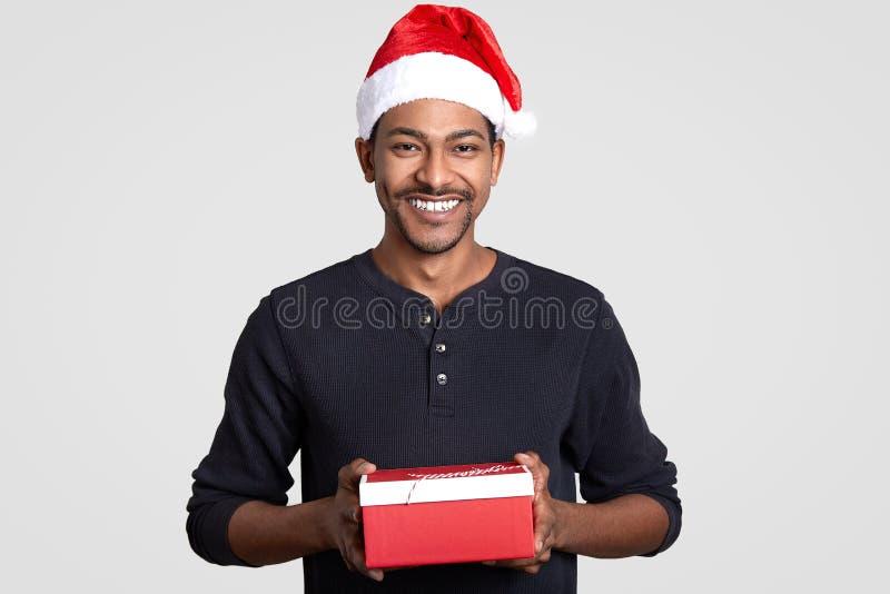 O tiro horizontal do homem alegre com sorriso toothy, veste o chapéu de Santa Claus, guarda a caixa de presente vermelha, feliz r foto de stock royalty free