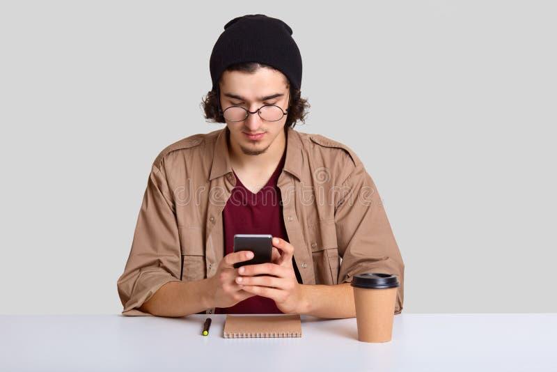 O tiro horizontal do jovem sério no chapéu elegante preto e na camisa ocasional, guarda o telefone celular moderno, mensagens com foto de stock royalty free