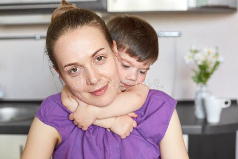 O tiro horizontal do menino pequeno dá o abraço morno a sua mãe, pose junto contra o interior da cozinha, indo cozinhar a ceia At foto de stock royalty free