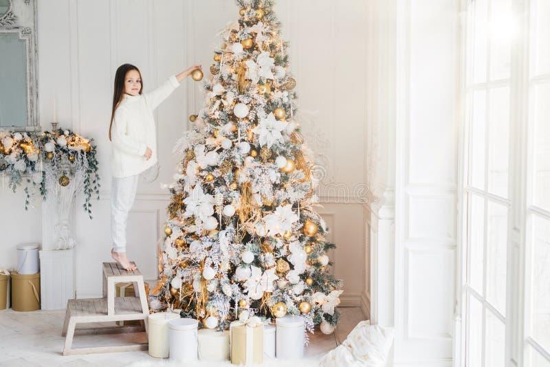O tiro interno da criança adorável está na cadeira na ponta do pé, decora a árvore grande do ano novo, tem o bom humor, sendo na  fotos de stock