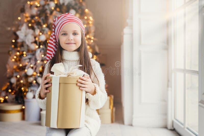 O tiro interno da criança pequena de vista agradável com os olhos encantadores azuis, veste o chapéu de Santa, posses atuais na c imagens de stock