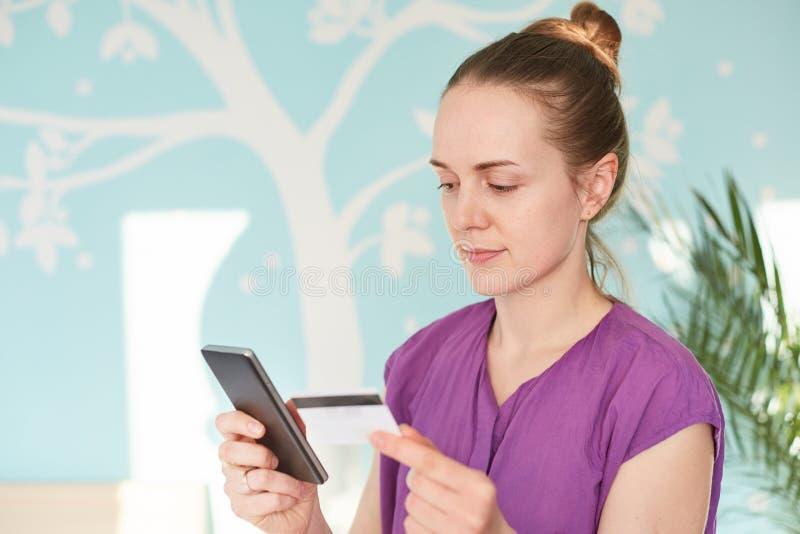 O tiro interno da dona de casa guarda o telefone celular e o cartão do plástico, faz a compra em linha, escolhe o que comprar, le imagem de stock