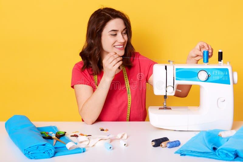 O tiro interno da mulher de sorriso encantador que põe a linha sobre a máquina de costura, sendo no bom humor, gosta de seu traba imagens de stock royalty free