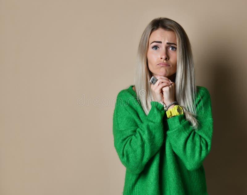 O tiro interno da mulher triste mantém as palmas junto, beggs para algo, sente-as pesaroso e culpado foto de stock