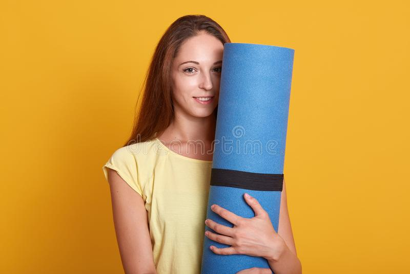 O tiro interno do atleta bonito novo da mulher que veste a camisa de t está guardando a esteira azul da aptidão e de vista a câme imagem de stock