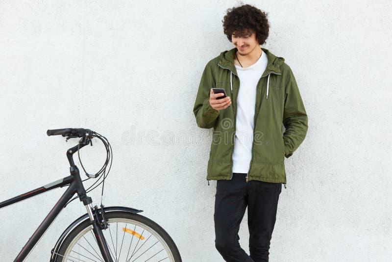 O tiro interno do jovem masculino atrativo vestido na roupa elegante, aprecia uma comunicação em linha através do telefone celula foto de stock