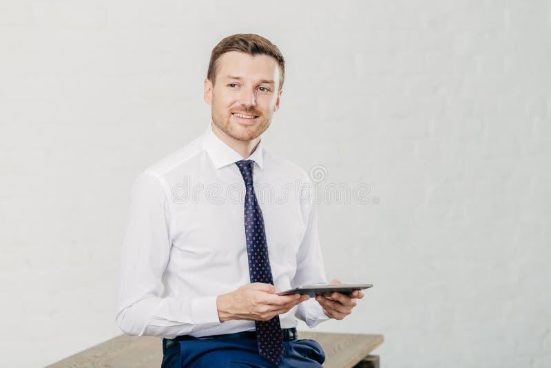 O tiro interno do proprietário masculino satisfeito da empresa próspera vestiu-se na roupa formal, guarda o tablet pc moderno, ap imagem de stock