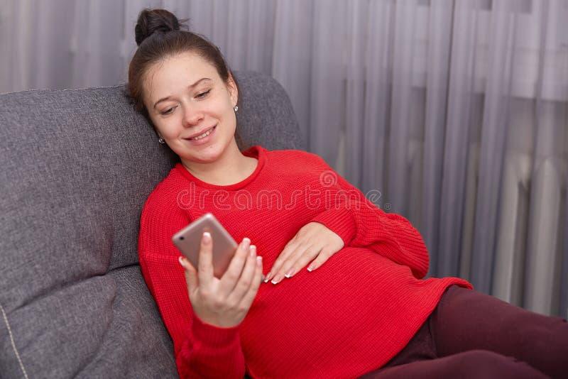 O tiro interno do telefone esperto da terra arrendada f?mea gr?vida feliz, da camiseta vermelha vestindo e dos leggins, tem o gru fotos de stock royalty free