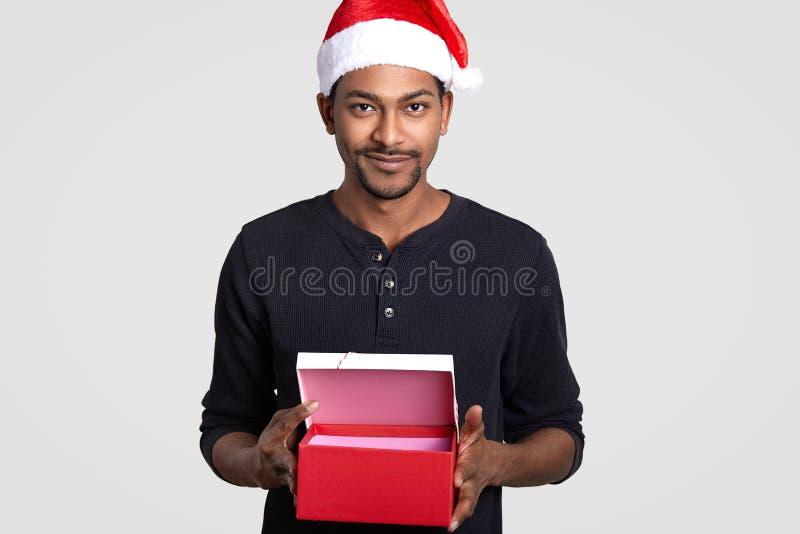 O tiro isolado Cropped do homem novo descascado escuro veste o chapéu de Santa Claus, leva a caixa de presente vermelha aberta, s imagens de stock