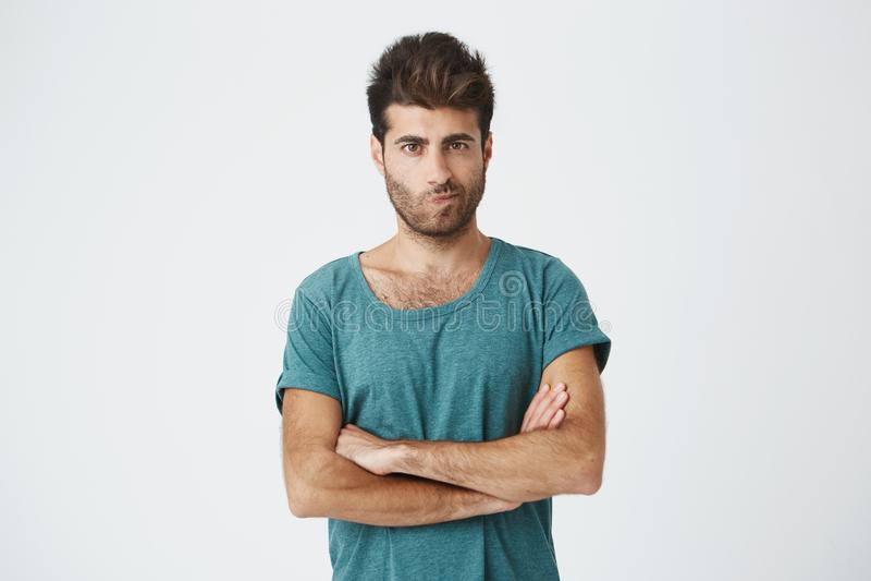 O tiro isolado do homem irritado que veste o t-shirt azul com o penteado à moda que guarda os braços cruzou-se, tendo cético e fotografia de stock