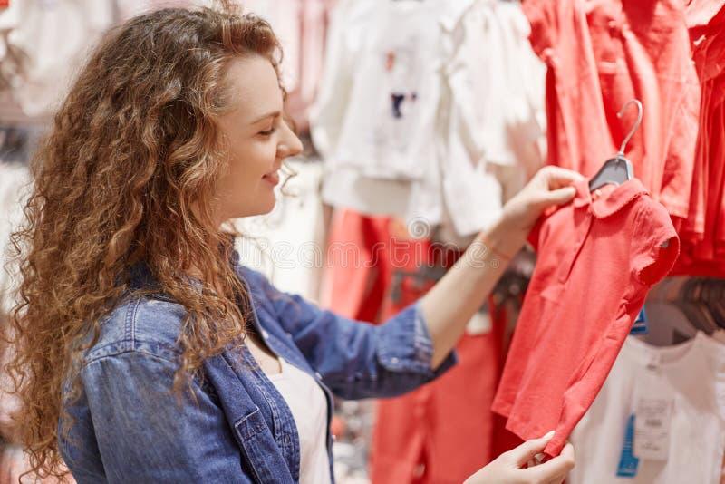 O tiro lateral da mãe nova encaracolado escolhe a camisa de t para sua filha pequena, estando no humor do bom como os gostos que  fotografia de stock