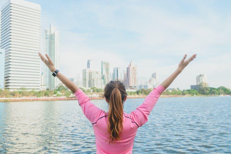 O tiro traseiro da mulher asiática nova relaxa-se e aquece-se para baixo após exercício running da cidade com um fundo da opinião imagens de stock royalty free