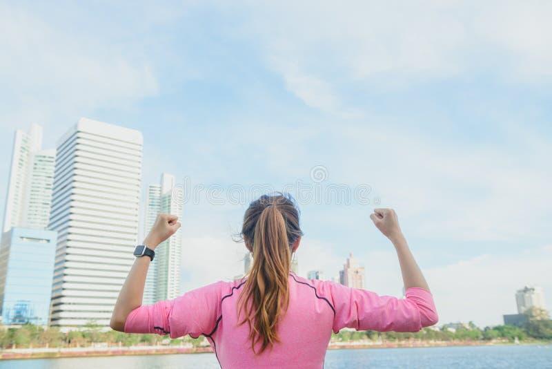 O tiro traseiro da mulher asiática nova relaxa-se e aquece-se para baixo após exercício running da cidade com um fundo da opinião fotos de stock