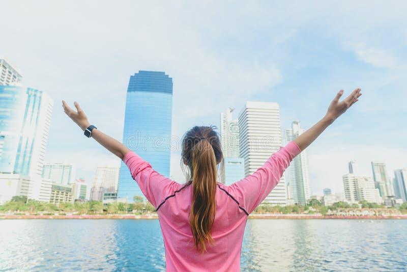 O tiro traseiro da mulher asiática nova relaxa-se e aquece-se para baixo após exercício running da cidade com um fundo da opinião fotografia de stock