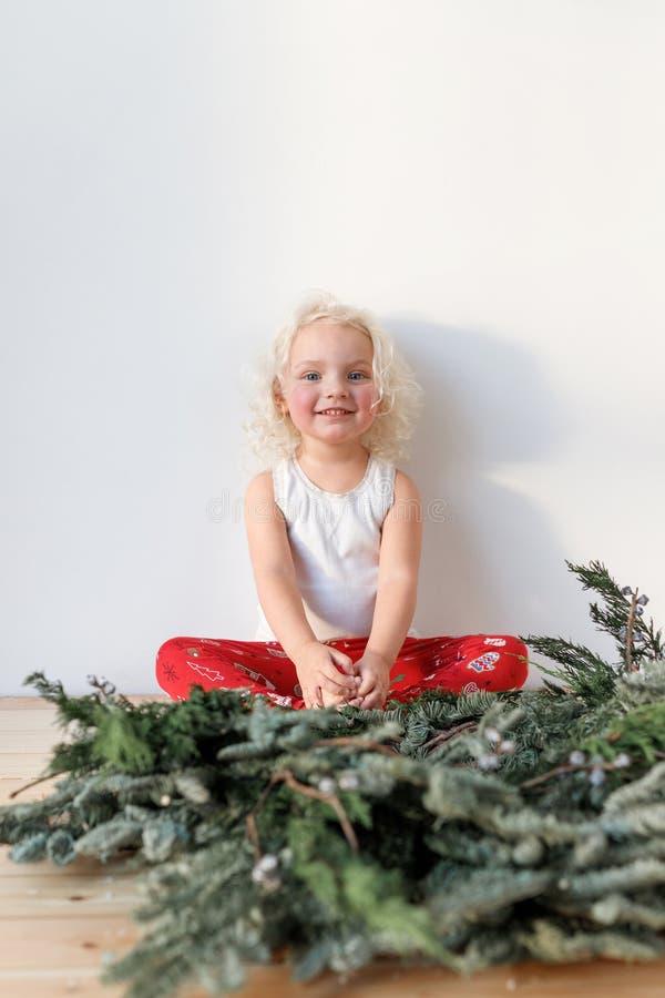 O tiro vertical da menina pequena bonita bonito senta os pés cruzados contra o fundo branco, tem a expressão feliz, exulta fotografia de stock