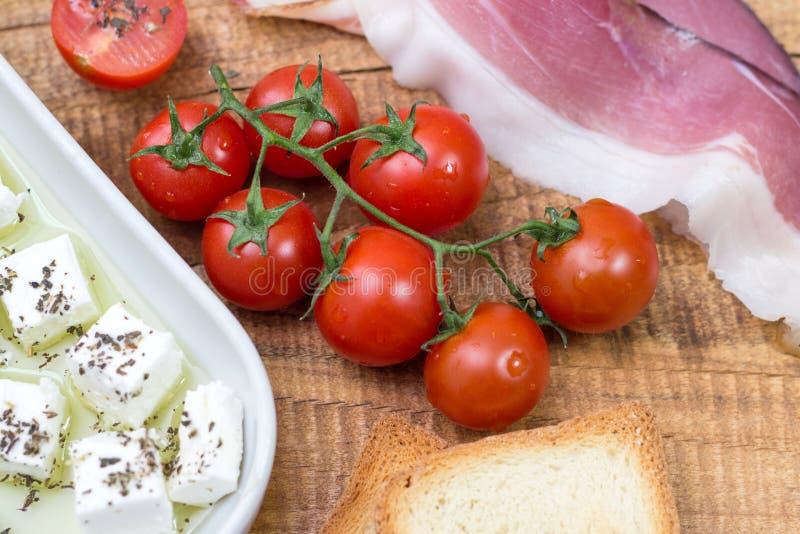 O tomate de cereja, queijo no azeite com manjericão, brindou o grânulo e o prosciutto no fundo de madeira fotos de stock royalty free