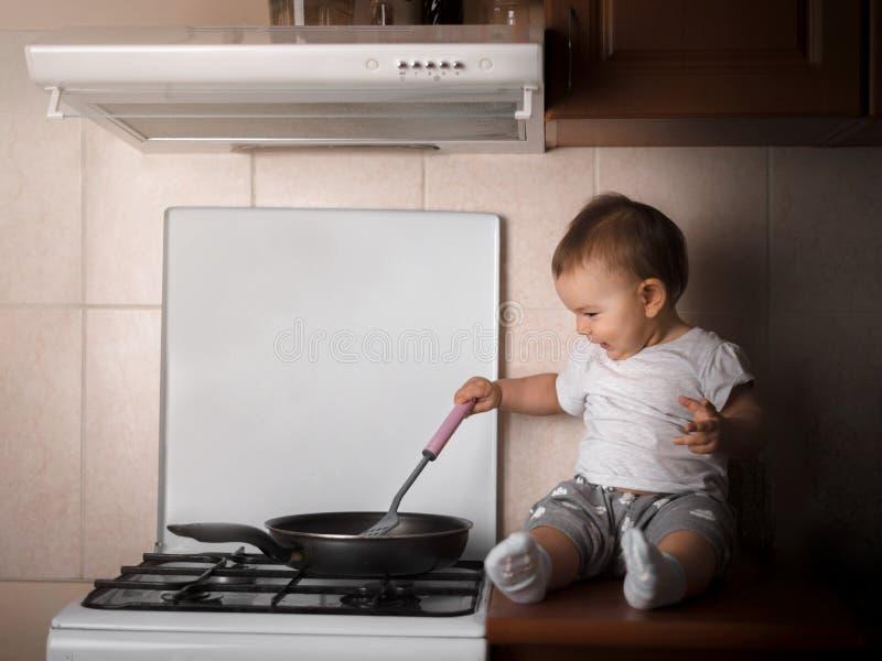 O toodler do bebê que prepara o jantar na cozinha no rico escuro da frigideira aquece-se fotos de stock