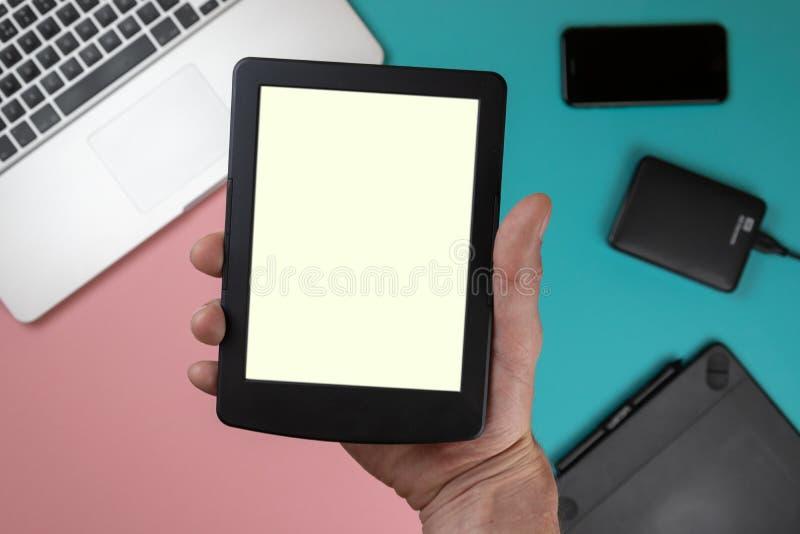 O toque da mão na tela vazia da tabuleta acima da opinião de tampo da mesa colorida, deixa o espaço para a exposição de seu índic imagem de stock