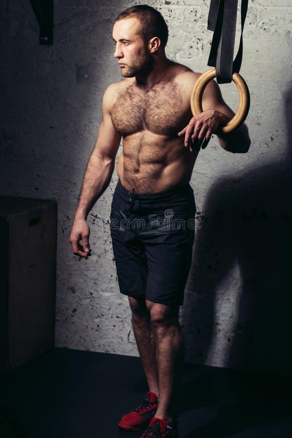 O torso despido do homem atrativo muscular novo que levanta contra a ginástica soa foto de stock