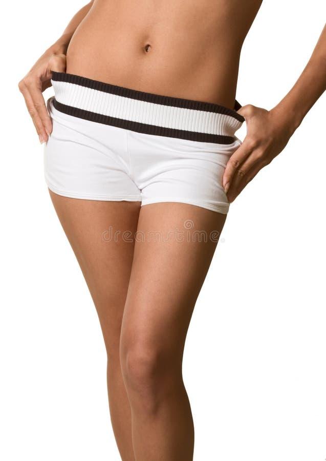 O torso e os quadris da mulher em shorts do branco descobrem a barriga imagem de stock royalty free