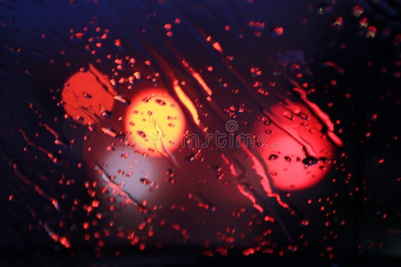 O tráfego é visto através do para-brisa do carro coberto na chuva, fundo bonito da chuva e das luzes fotos de stock