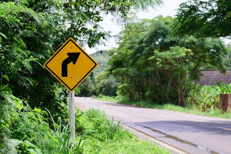 O tráfego de advertência do direito da volta assina o campo é cercado dentro por árvores verdes fotos de stock