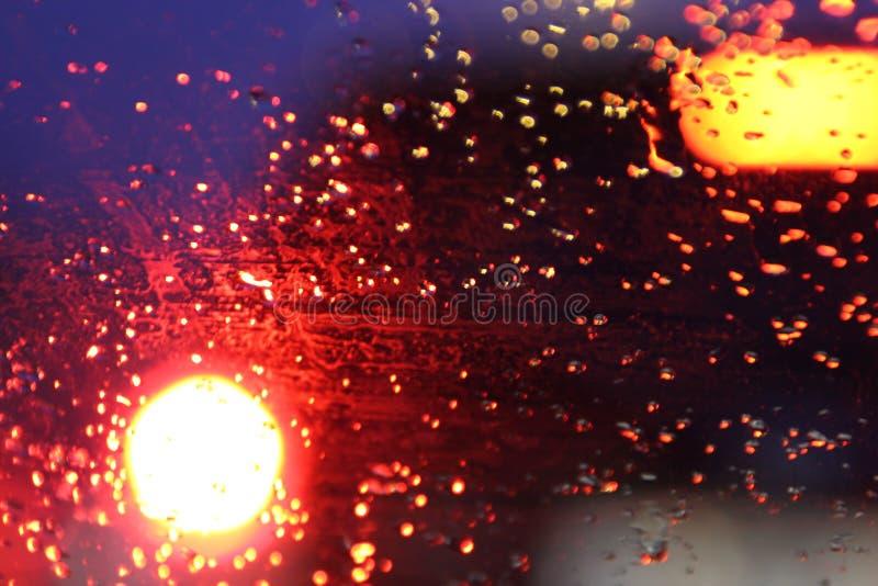 O tr?fego ? visto atrav?s do para-brisa do carro coberto na chuva, fundo bonito da chuva e das luzes imagens de stock