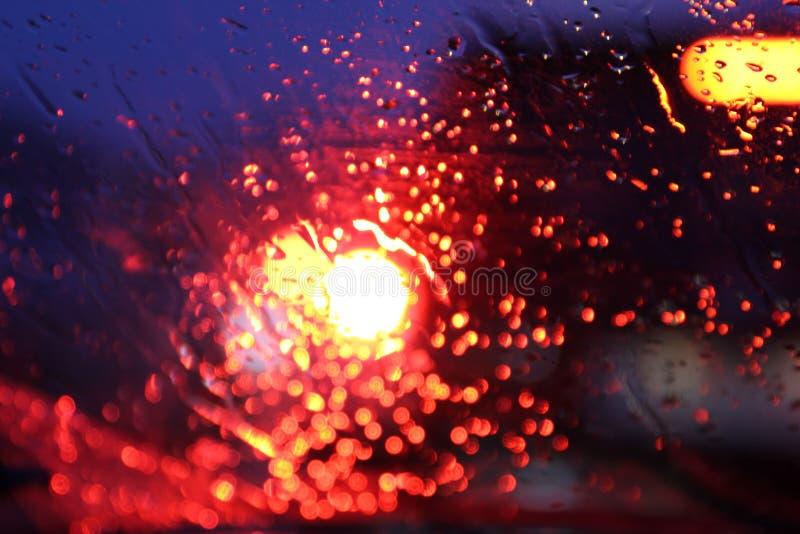 O tr?fego ? visto atrav?s do para-brisa do carro coberto na chuva, fundo bonito da chuva e das luzes foto de stock royalty free