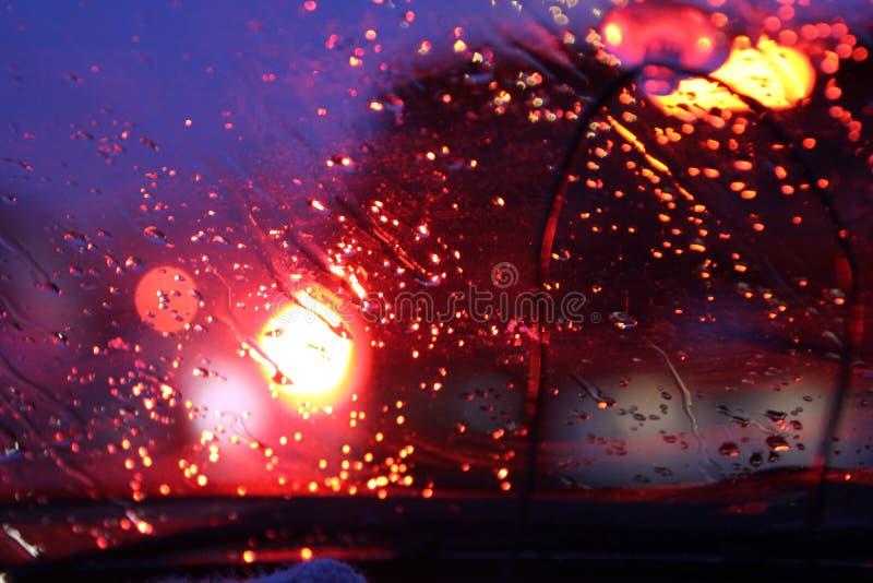 O tr?fego ? visto atrav?s do para-brisa do carro coberto na chuva, fundo bonito da chuva e das luzes imagem de stock