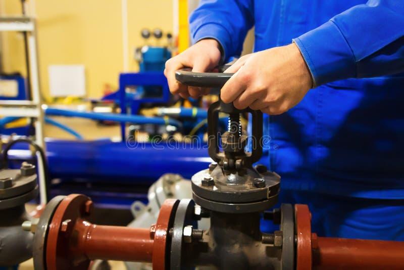 O trabalhador abre a válvula no encanamento na planta industrial fotografia de stock royalty free