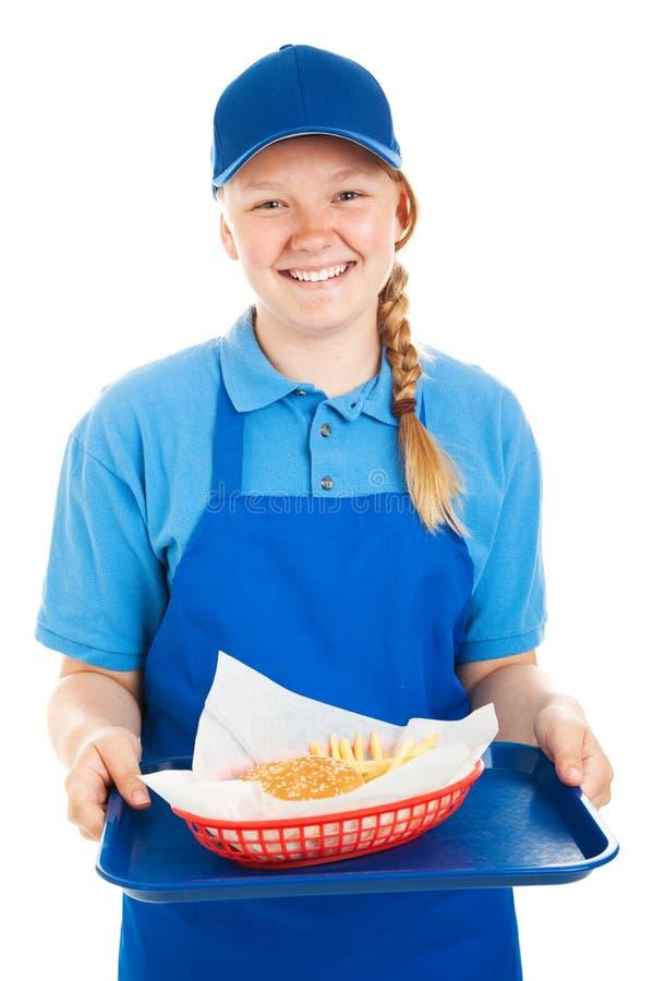 O trabalhador adolescente serve o hamburguer e frita-o imagens de stock