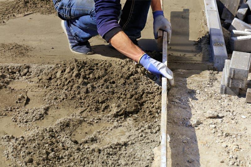 O trabalhador alinha a fundação com uma prancha de madeira para colocar telhas no passeio fotos de stock