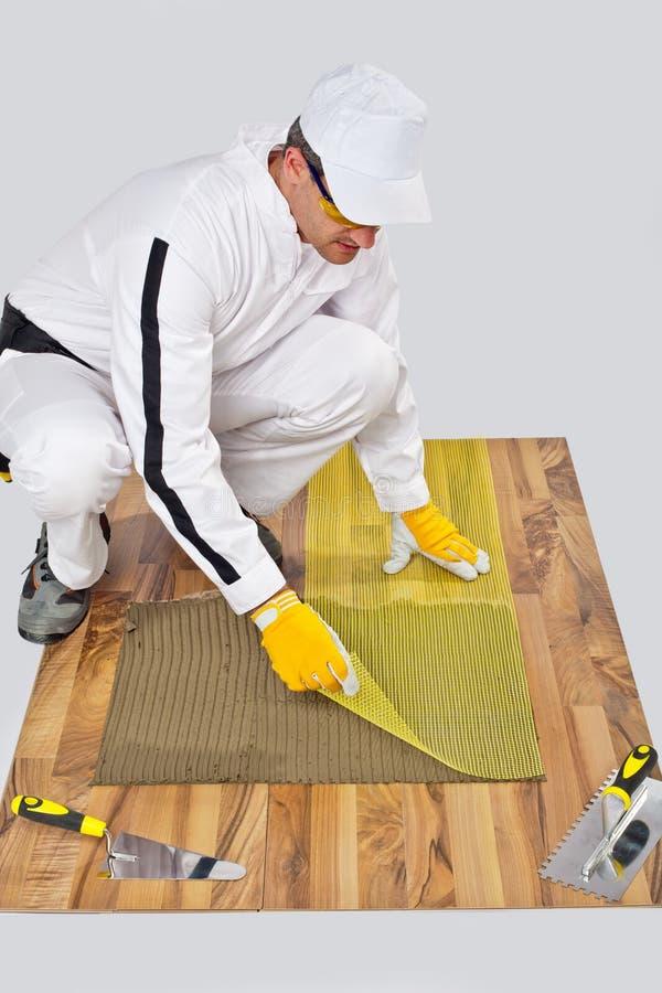 O trabalhador aplica o engranzamento da fibra no adesivo da telha foto de stock