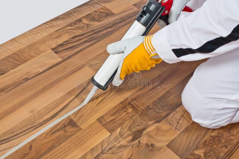 O trabalhador aplica o vedador do silicone no assoalho de madeira foto de stock royalty free