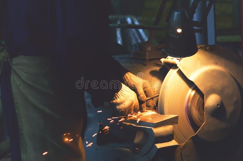 O trabalhador aponta a ferramenta em uma roda de moedura de giro fotografia de stock