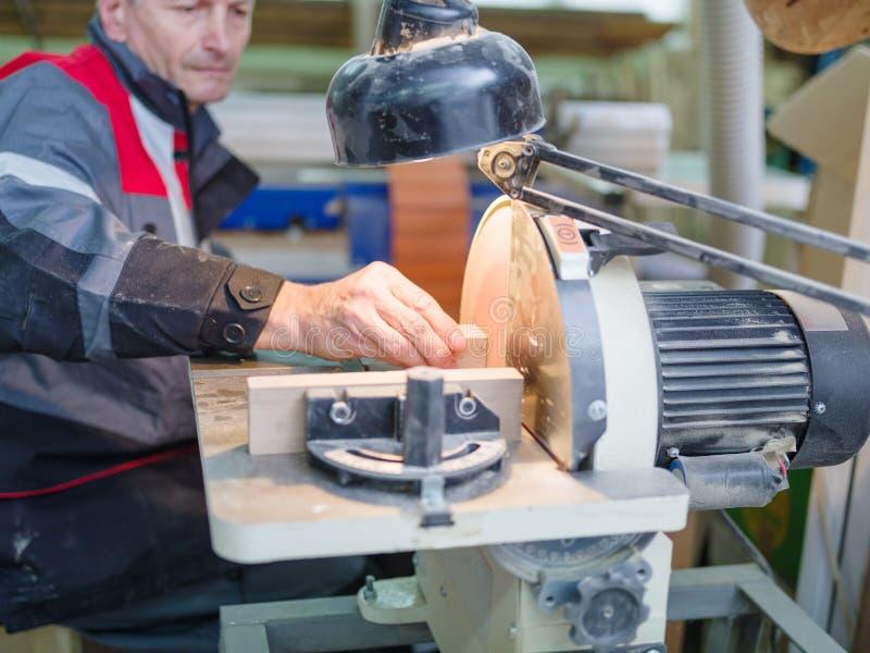 O trabalhador aponta a peça sob a luz do ` s da lâmpada fotos de stock