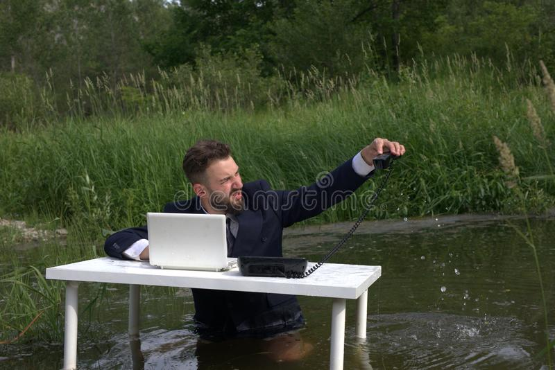 O trabalhador cansado, gerente, empregado do centro de atendimento jogou o telefone na água foto de stock royalty free