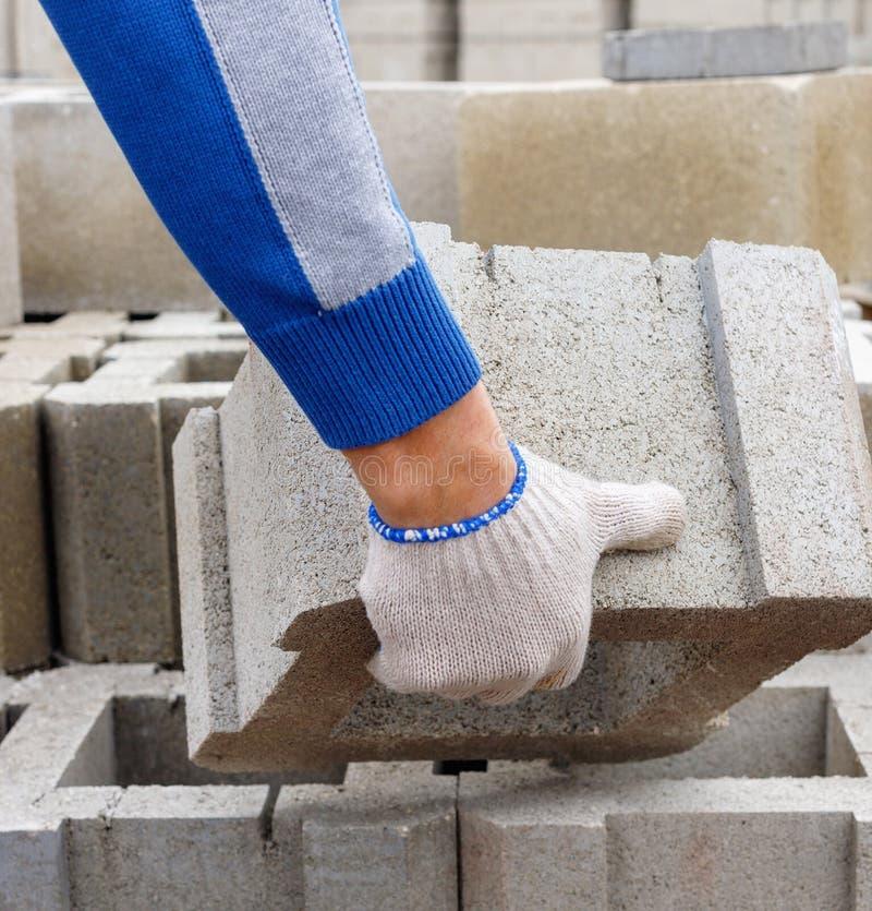 O trabalhador carrega blocos de cinza da pasta do cimento para a construção fotografia de stock royalty free