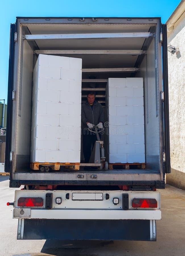 O trabalhador carrega o semi-caminhão fotos de stock