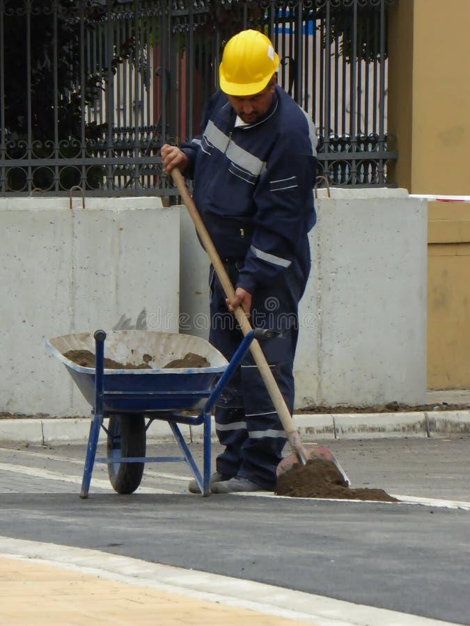 O trabalhador carrega a pá com a areia no carrinho de mão com pá foto de stock