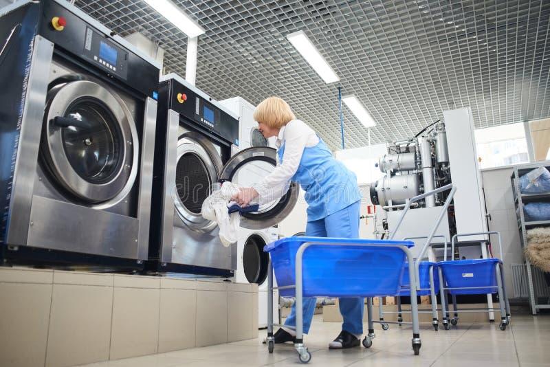 O trabalhador carrega a roupa da lavanderia na máquina de lavar foto de stock