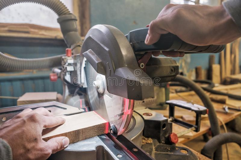 O trabalhador caucasiano do carpinteiro do homem que trabalha conduzindo a circular viu para cortar placas imagem de stock
