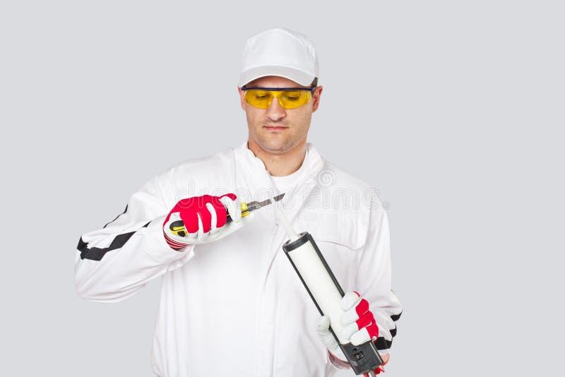 O trabalhador com faca remove o silicone do vedador do tampão do corte foto de stock