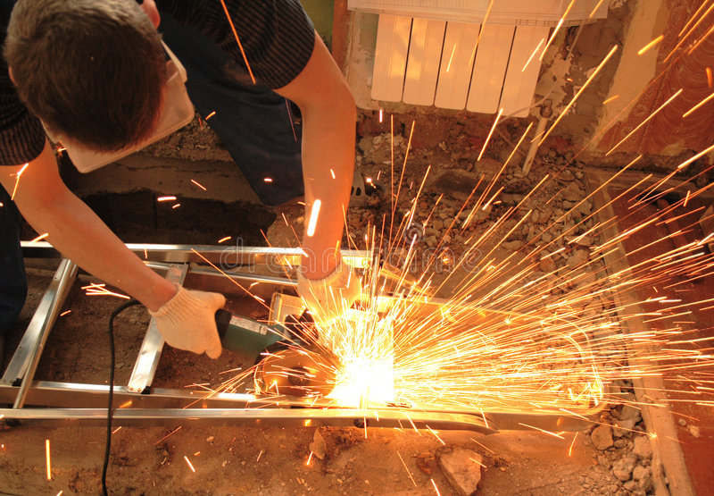 O trabalhador com moedor de ângulo imagens de stock