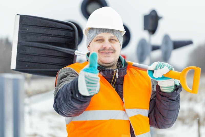 O trabalhador com a pá da neve perto do sinal ilumina no dia nevado imagem de stock