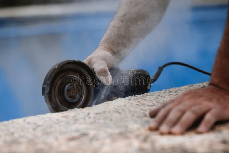 O trabalhador com radial viu com poeira no ar com fundo azul fotos de stock
