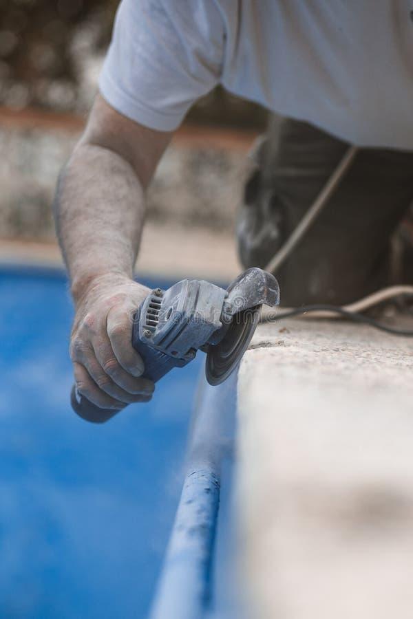 O trabalhador com radial viu com poeira no ar com fundo azul imagem de stock royalty free