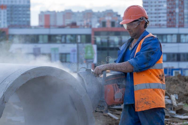 O trabalhador corta o anel concreto no canteiro de obras imagens de stock